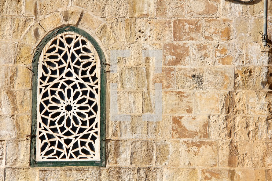 Ornate arched window grate in a stone wall.