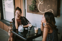 girlfriends talking at a table outdoors at a coffee shop