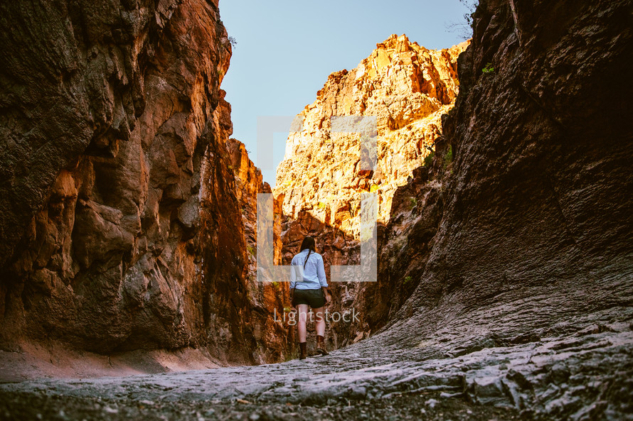 A woman hiking among steep cliffs.