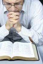 a man praying over the pages of a Bible