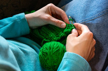 woman knitting green yarn