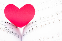 red paper heart on sheet music