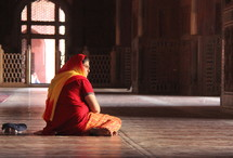 woman sitting in prayer inside a Mosque