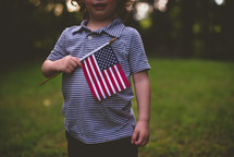 toddler holding an American flag over his heart