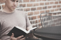 man reading a Bible outdoors sitting at a table