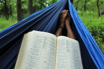reading a Bible in a hammock