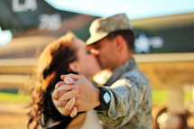 a military couple kissing