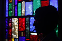 silhouette of a man's head and a stained glass window