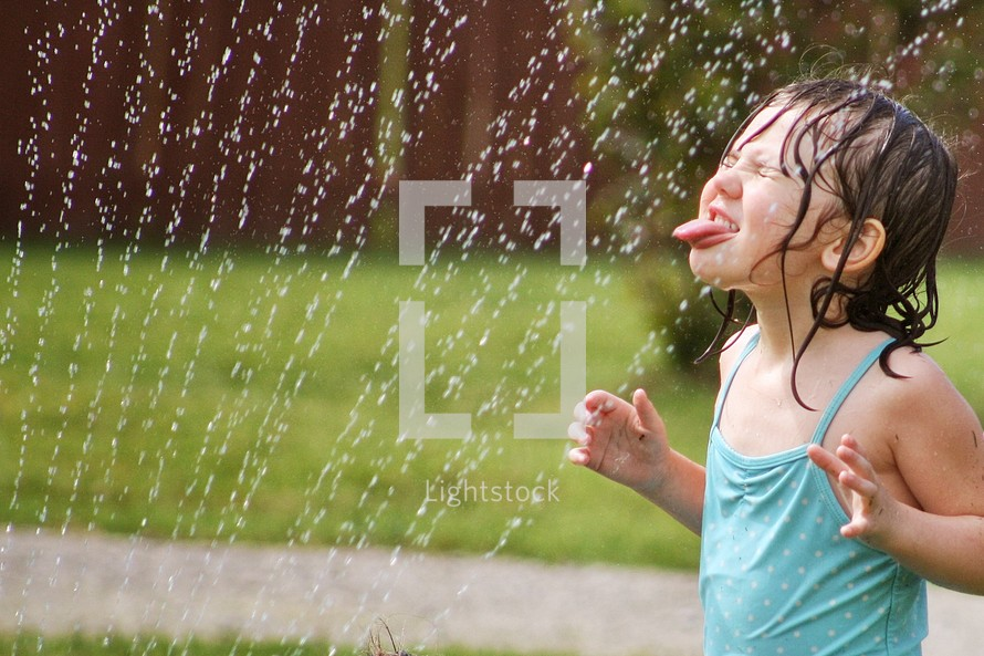 girl child playing in a sprinkler