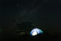 A brightly lit tent set up under the stars.