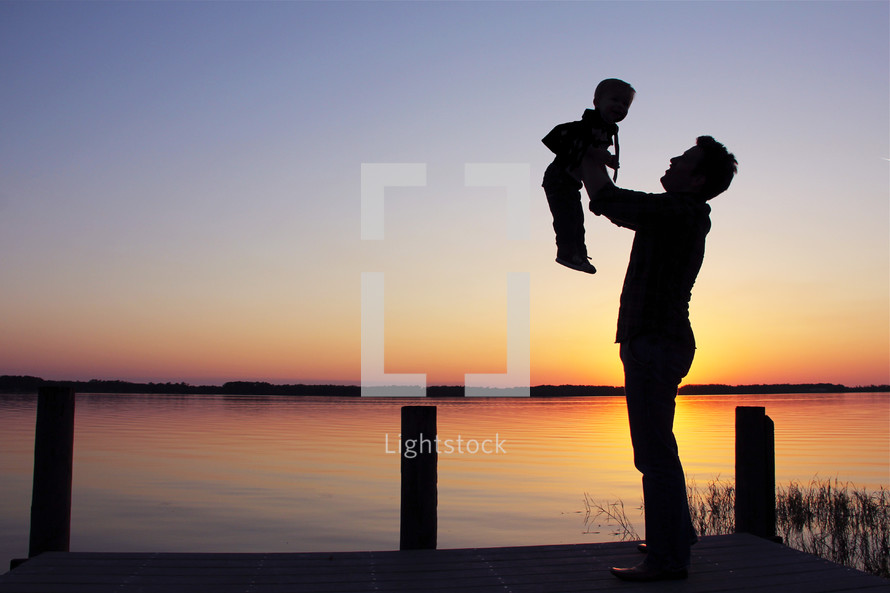Silhouette of a father holding up his son in front of a lake as dawn breaks behind them.