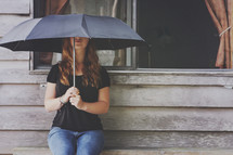 a girl sits alone with umbrella