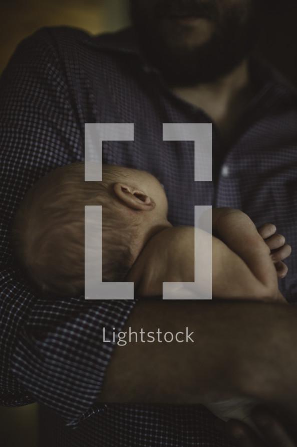 a father cradling a newborn
