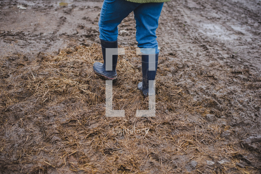 rain boots walking through mud on a farm