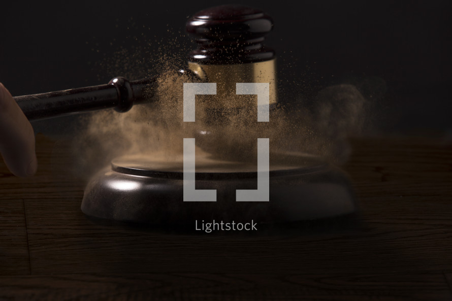 banging gavel with dust.