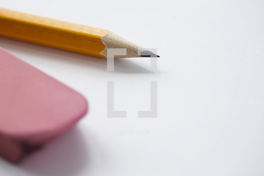 sharpened pencil and eraser on white.