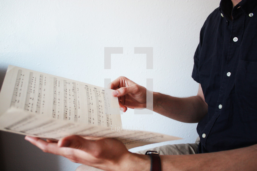 a man looking a sheet music