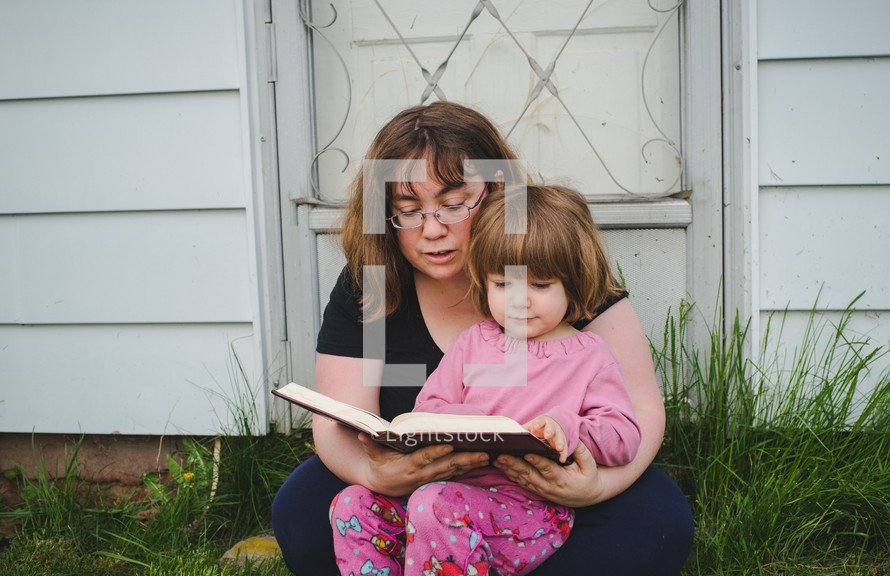 mother and daughter reading a Bible together outdoors