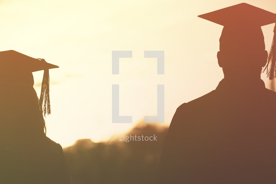 silhouettes of graduates in cap an gowns at sunset.