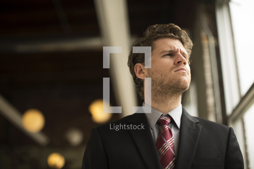 Millennial in a suit and tie looking away in thought in an office.