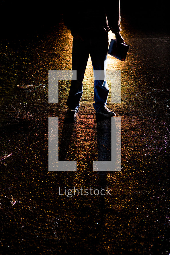Silhouette of a man holding a Bible standing in front of a light.