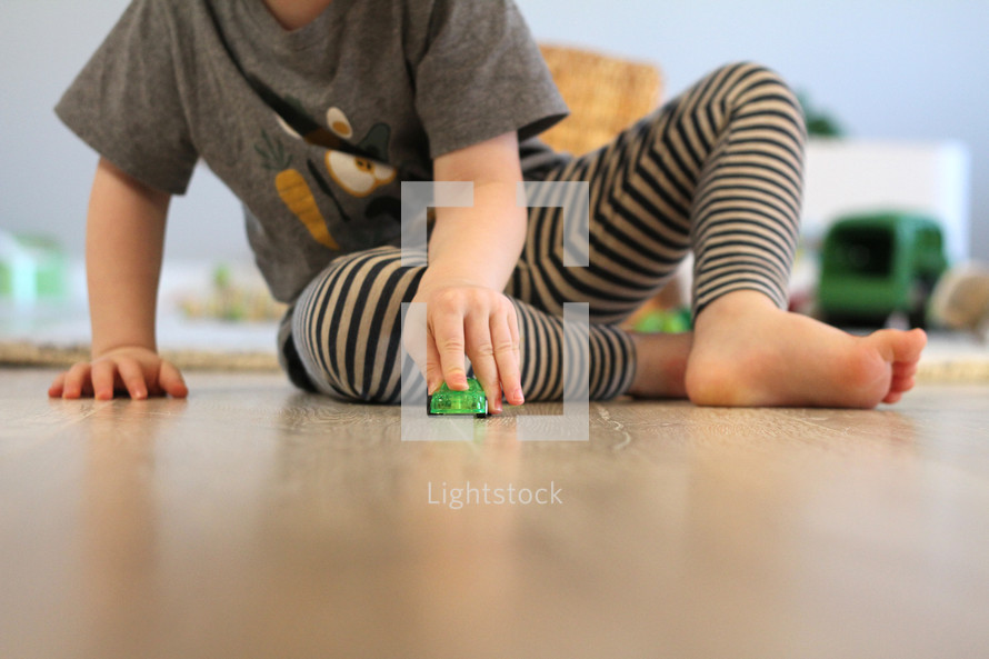 toddler playing with a toy car