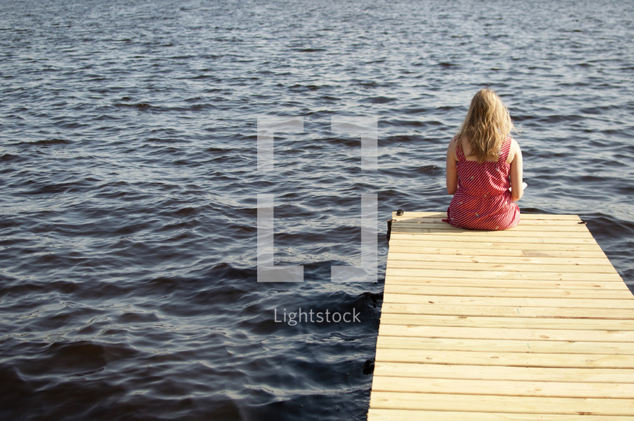 woman reading a Bible sitting at the end of a dock