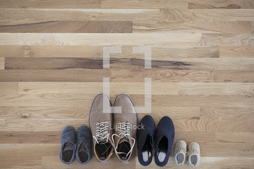 pairs of difference sizes of shoes on a wood floor