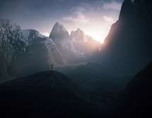 A woman lifts her arms in praise as the sun rises in the mountains