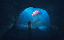 Little girl in cave looks at a beautiful cherry tree