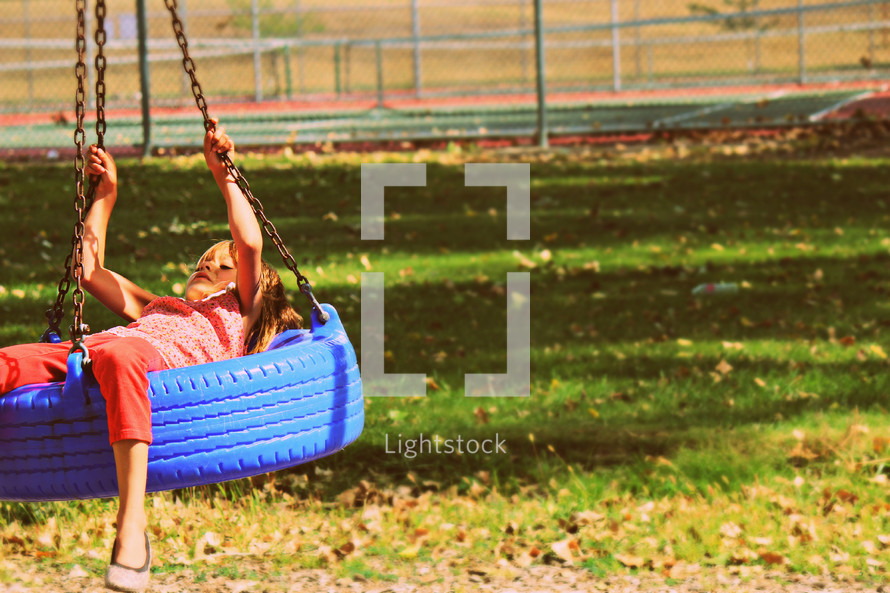 child on a tire swing
