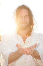 Smiling Jesus with outreached hands in the sunlight.