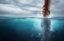 A hand reaches down into the water and saves someone drowning.