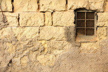Barred window in weathered stone wall