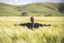 a woman standing in a field of wheat with outstretched arms