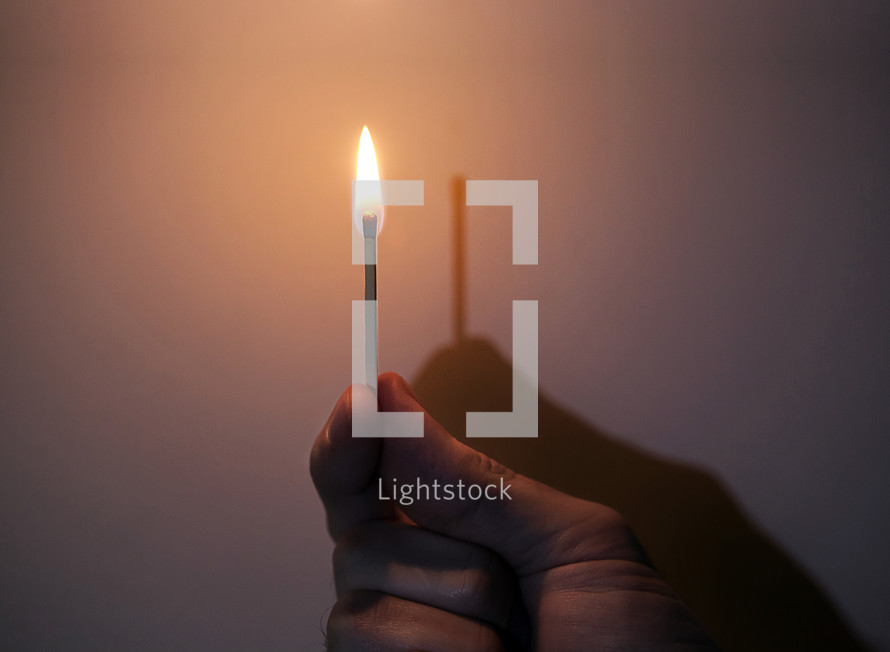 "hand holding a match, flame has no shadow, ""I am the light"""