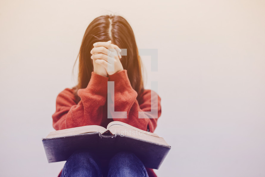 a woman praying over a Bible in her lap