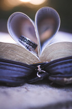 rings on the pages of a Bible and heart shaped folded pages