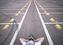 man lying down in a parking lot