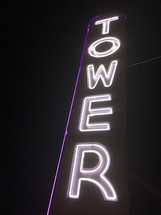 "A tall neon sign with the word ""Tower."""