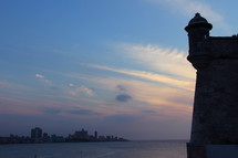 Havana bay at sunset. Turret of Castle Morro protecting the entrance to the harbor.