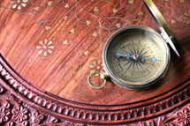 Brass magnetic compass on oriental wooden desk