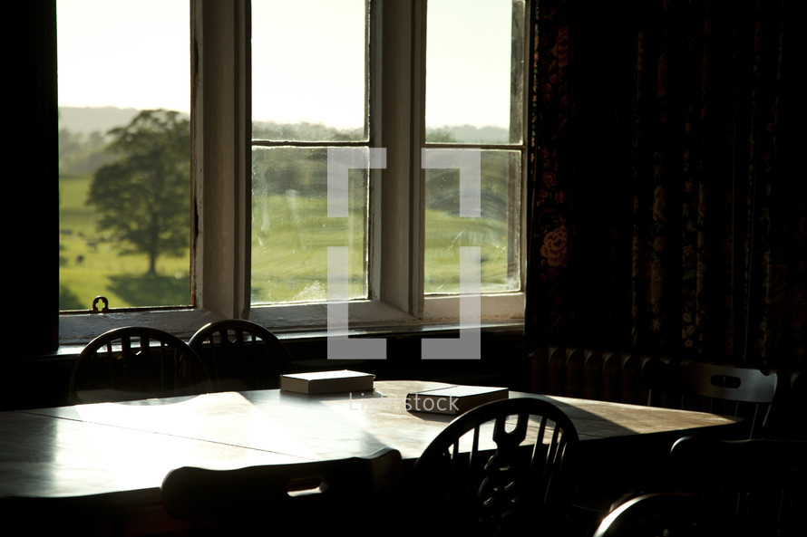 Bibles on a dining room table in a window