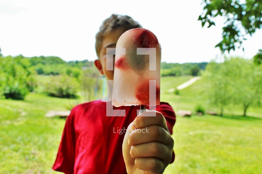 a boy holding a popsicle