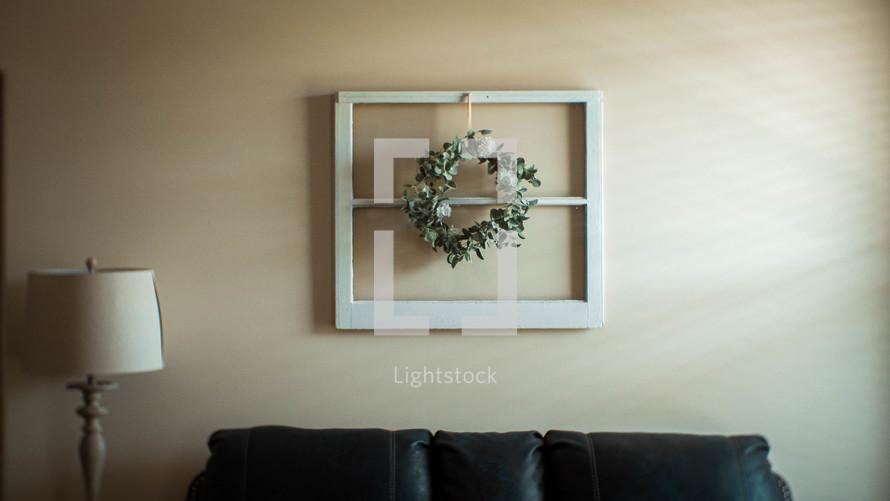 eucalyptus wreath on an old window over a couch