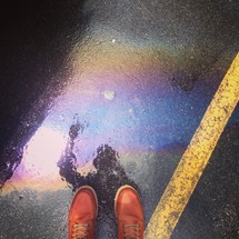 feet and a reflection in a puddle