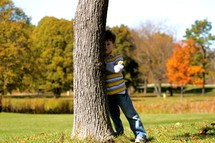 a boy child hiding behind a tree