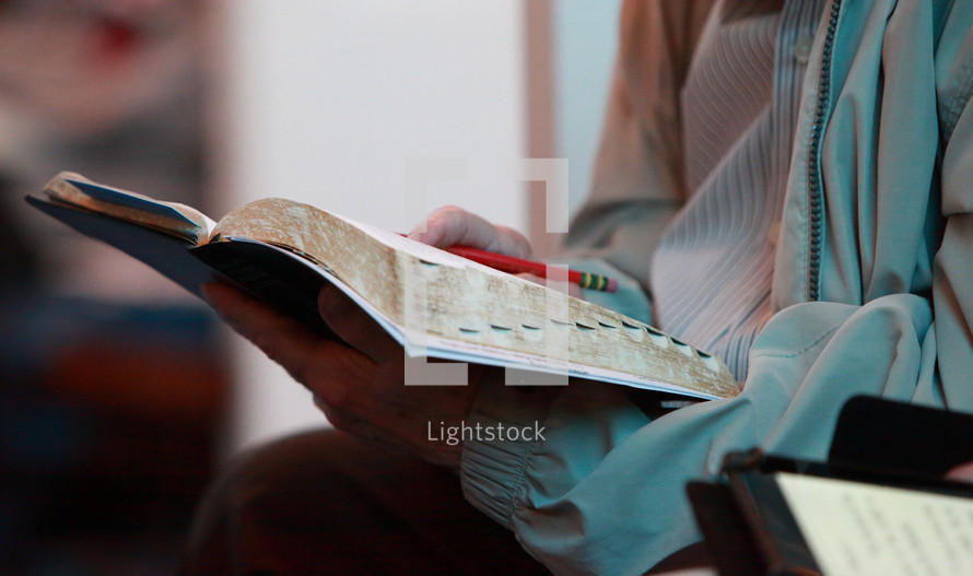 an elderly woman reading a Bible