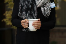 a woman standing outdoors in a scarf holding a mug