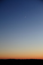crescent moon in an evening sky
